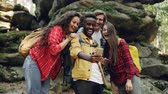 ハイカー : Happy African American guy is making video call using smartphone during hike in forest with friends, young people are looking at screen, waving hand and talking. 動画素材