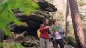 montrer du doigt : Cheerful travelers are looking at map standing in wood near rocks discussing way and looking around through binoculars then walking in chosen direction.