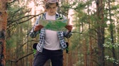 direito : Handsome young man traveler is walking in forest then standing and looking at map searching for right way then going away. People, travelling and adventures concept. Stock Footage