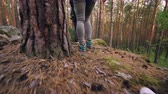expedição : Low angle shot of travelers legs in sneakers walking in wood exploring new territory stepping on covered with grass and moss ground. People and tourism concept.