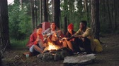 кондитерские изделия : Tourist is playing the guitar sitting near campfire with friends singing and having fun, young people are holding sticks with marshmallow above flame. Food, music and fun concept.