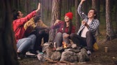 eğlenceli : Happy male and female friends are doing high-five and eating warm marshmallow on campsite sitting around fire and having fun. Food, nature and youth concept. Stok Video