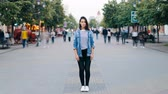 metropolitano : Time-lapse portrait of stressed young woman standing alone in city center wearing jeans and denim jacket and looking at camera while people are passing by.