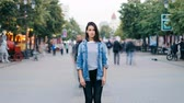 zoom out : Zoom out time-lapse of beautiful lady with dark hair standing alone among crowd of people and looking at camera. Modern life, society and loneliness concept. Stock Footage