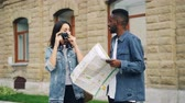eğlenceli : Happy African American guy and Caucasian girl travelers are looking at map and taking photos standing outdoors then leaving. Multiracial friendship and tourism concept. Stok Video