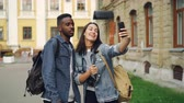 рюкзак : Beautiful multiracial couple is talking with friends online making video call using smartphone standing in the street with backpacks. Travelling and technology concept.