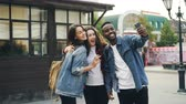 estrangeiro : Happy African American guy is taking selfie with friends beautiful Caucasian girls standing in street posing and holding smartphone during journey in foreign country.