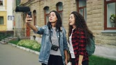 рюкзак : Emotional young women travelers are making online video call using smartphone holding device and talking showing historical building behind them expressing excitement.