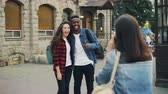 рюкзак : Young woman is taking pictures of beautiful couple African American guy and Caucasian girl standing in the street and posing for camera. Tourism, technology and friends concept.