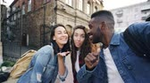 mnohorasový : Point of view shot of attractive young men and women travelers taking selfie in the street posing and laughing holding camera. Modern technology and travelling concept.