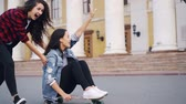 empurrando : Slow motion of happy young woman sitting on longboard and laughing while her female friend is pushing her moving skateboard having fun in city. Friendship and joy concept.