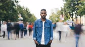 bolso : Time-lapse portrait of African American man in casual clothes looking at camera standing in busy street downtown suffering from loneliness when people are passing by.