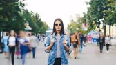 натюрморт : Time-lapse portrait of attractive brunette in sunglasses standing in the street by herself and looking at camera when men and women are passing by on autumn day.