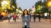пересек : Time-lapse of good-looking woman towny in denim clothing standing alone in the street among crowds of people and looking at camera. Street lights are visible.