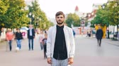 натюрморт : Time-lapse portrait of serious young man looking at camera standing in center of busy pedestrian street in summer wearing stylish clothing while people are passing by. Стоковые видеозаписи