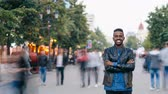 kozmopolita : Time-lapse of smiling African American man standing alone in city center with hands crossed enjoying city life and looking at camera. Youth and lifestyle concept.
