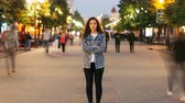 пересек : Zoom in time-lapse of stylish young lady tired of usual haste standing in the street among whizzing people and looking at camera. Time, youth and society concept.