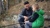 fangen : Bearded young man is fishing with cute child on autumn day, boy is holding rod and talking to father learning to catch fish. People, sharing experience and family concept. Stock Footage