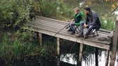 chytil : Good-looking man and his cute son are fishing in pond from wooden dock sitting on chairs with rods and talking. Loving family, common hobby and generations concept.