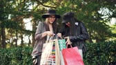 ask : Two young women shopaholics are talking in the street looking at purchases in bags and expressing excitement. Shopping, people and happiness concept. Stock Footage