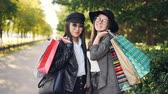 fantaisie : Portrait of beautiful young women shoppers standing in the street holding paper bags and smiling looking at camera. Youth lifestyle and consumerism concept.