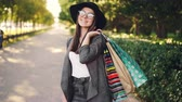 paper bag : Portrait of pretty young woman holding paper bags standing outdoors in the city and looking at camera on sunny autumn day. Shopping, youth and street concept. Stock Footage