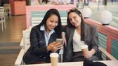 zum mitnehmen : Pretty young ladies friends are using modern smartphone sitting at table in cafe with take away coffee. Happy girls are touching screen, watching photos and laughing. Stock Footage