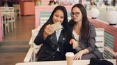 fotografia : Pretty Asian girl is taking selfie with her Caucasian friend sitting at table in cafe then watching photos. Interethnic friendship, modern technology and photography concept.