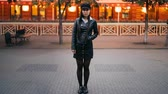 bolso : Time-lapse portrait of serious Asian woman in stylish clothes standing in the street in the evening and looking at camera when crowds of men and women are passing by.