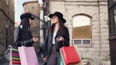 begegnen : Cute Asian girl is talking to her Caucasian friend elegant brunette standing in the street holding shopping bags and laughing. People, city and shopaholics concept.