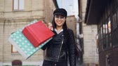 bolsas de papel : Slow motion portrait of smiling Asian woman shopaholic walking in the street with paper bags, turning and looking at camera enjoying purchases and city.