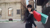 bolsas de papel : Slow motion portrait of good-looking Asian woman turning to camera and smiling walking with paper bags from shop enjoying city and shopping in free time.