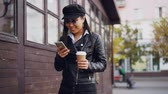 mensageiro : Slow motion of happy Asian girl using smartphone while walking in the street wearing leather jacket and holding coffee. Urban lifestyle, millennials and young people concept.