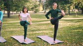 instrutor : Professional yoga instructor is teaching students to do balancing exercise, teacher is speaking and showing pose while young women are repeating standing on mats.