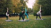 インストラクター : Young ladies in sports clothing are exercising in park doing yoga on mats on green and yellow grass. Healthy lifestyle, modern youth and autumn nature concept.