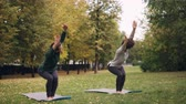 инструктор : Flexible girls are practising Chair position standing on yoga mats in park and moving body and head. Beautiful autumn nature, trees and grass are visible.