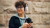 eğlenceli : Pretty girl is headphones and glasses is listening to music and touching smartphone screen choosing songs standing outdoors in city with stone wall in background.