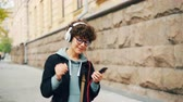 prazer : Good-looking brunette in stylish glasses is listening to radio in headphones and using smartphone during walk in modent city in autumn. People and urban life concept.