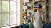 inovador : Happy young lady is wearing artificial reality glasses standing at home in loft style apartment and gesturing. Curly-haired girl is wearing casual clothing.