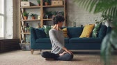 ev geliştirme : Beautiful woman is finishing her yoga practice and relaxing in lotus position with hands on knees breathing and enjoying relaxation. Meditation and sports concept. Stok Video