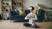 ar : Slim young lady in artificial reality glasses is meditating at home in lotus pose with hands in namaste enjoying simulation and relaxing. Modern technology and experience concept.