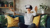 inovador : Zoom-in of smiling young lady in augmented reality glasses moving hands and turning head sitting on sofa at home and having fun. Entertainment and technology concept.