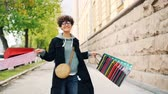 turns : Slow motion portrait of excited girl holding gift bags and spinning around looking at camera having fun. Shopping, youth lifestyle and modern city concept. Stock Footage