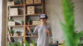 inovador : Amazed young lady is enjoying new experience in augmented reality glasses standing in flat and moving hands reaching in syberspace. Technology and fun concept.