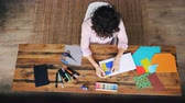 клей : Top view of young lady creative designer working in home office making collage from splash-paper cutting figures and sticking them in notebook. Art and work concept. Стоковые видеозаписи