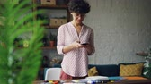 combles : Smiling curly-haired lady is taking pictures of desk creating flat lay using smartphone camera standing in modern apartment. Modern technology and design concept. Vidéos Libres De Droits
