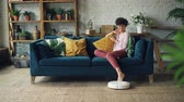 innovative technology : Joyful young woman is playing with robotic vacuum cleaner then using smartphone sitting on couch at home enjoying modern technology. People and innovations concept. Stock Footage