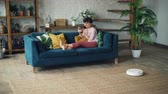 diário : Smiling young lady house owner is sitting on sofa in living room using smartphone while robotic hoover is cleaning floor doing domestic work. Inventions and everyday life concept. Vídeos
