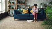 robótico : Attractive woman is turning on robotic vacuum cleaner sitting on sofa then using smartphone and resting while device is cleaning the house. Technology and apartments concept.