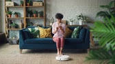 robótico : Cheerful young lady is turning on robotic hoover and enjoying automatic cleaning sitting on sofa and relaxing with smartphone. Modern technology and youth concept.